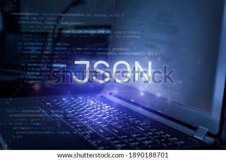 JSON inscription against laptop and code background. Technology concept.