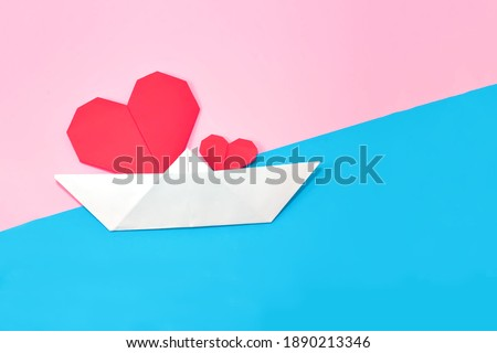 White paper boat with red paper origami hearts on an abstract pink - blue background.