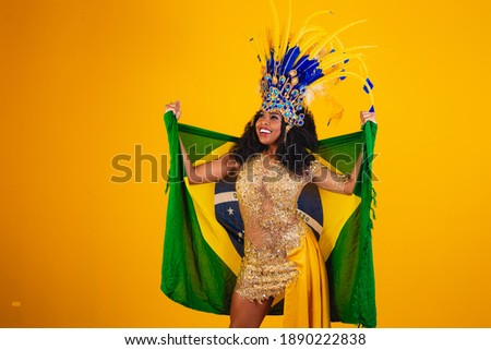 Brazilian afro woman posing in samba costume on yellow background with the flag of Brazil