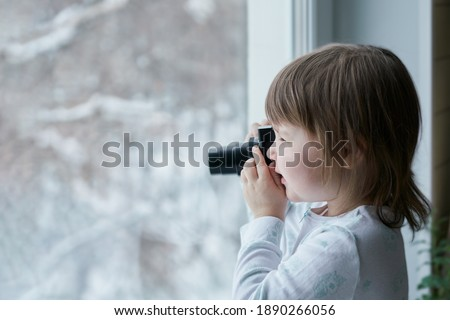 The baby takes pictures with a camera on a winter street. Selective focus. Copy space.