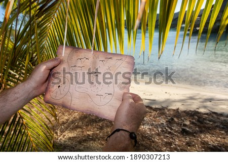 Searching for a buried treasure with a map on a deserted tropica Royalty-Free Stock Photo #1890307213