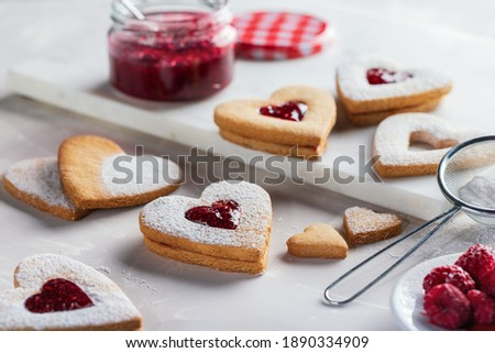 Image of heart-shaped cookies on light gray background. The middle of the cookies are filled with raspberry jam and sprinkled with powdered sugar. Valentine's Day or Christmas biscuits making process.