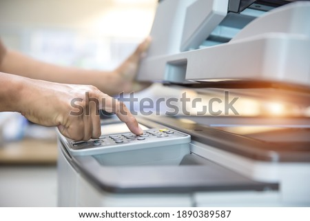 Close up hand of office man press the copy button on panel to using the copier or photocopier machine in copy room for scanning document printing a sheet and xerox photocopy. Royalty-Free Stock Photo #1890389587