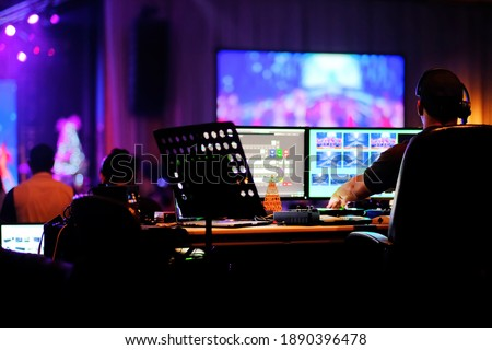 DJ technician engineer operating stage light live broadcast audio video equipment control center in computer monitors to switch camera scenes, music, sound, and lighting effects in holiday event show. Royalty-Free Stock Photo #1890396478
