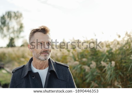 Serious man standing thinking outdoors at the coast alongside tall reeds looking off to the side with a contemplative expression Royalty-Free Stock Photo #1890446353