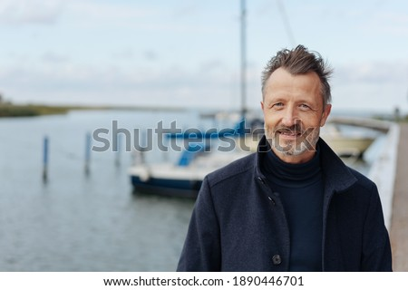 Man taking a stroll on a waterfront promenade in a warm overcoat on a cold autumn day in a close up portrait Royalty-Free Stock Photo #1890446701