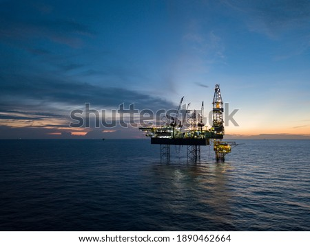 Aerial view offshore drilling rig (jack up rig) at the offshore location during sunset Royalty-Free Stock Photo #1890462664