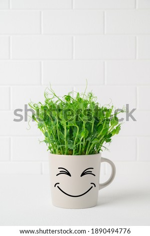 Gray mug with funny face in which grows pea microgreens on background white brick wall. Funny flower pot with a smiley face stands on table. Springtime home gardening concept. Copy space