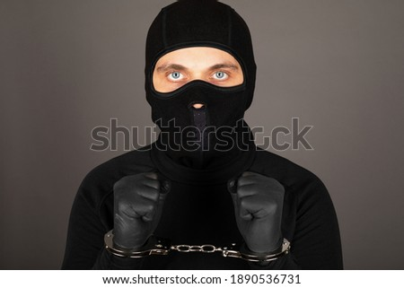 Picture of young man with black mask and outfit suspect of a robbery, wearing handcuffs in front of grey background