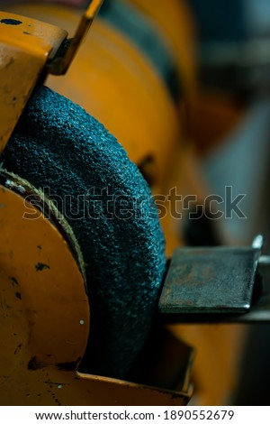 Industrial electric grinding machine for sharpening tools and knifes. Close up image with shallow depth of field.