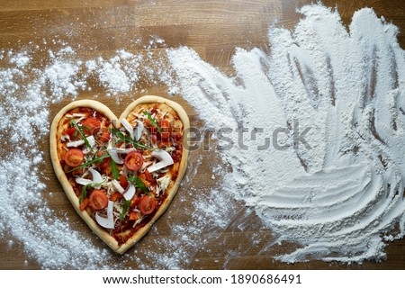 We are preparing a large holiday pizza in the shape of a heart with pepperoni and mushrooms at home for dinner for loved ones on a table with flour. Holiday concept in Italy with national dish.