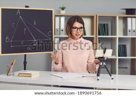Female math and geometry teacher explains new material to students through a video call using a phone on a tripod. Woman sits in a classroom with a blackboard next to her and conducts an online lesson