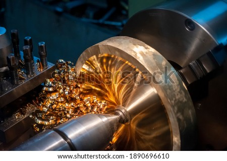 The operation of lathe machine cutting the brass material  parts with the cutting tools. The metalworking process by turning machine. Royalty-Free Stock Photo #1890696610