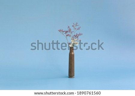 Dried flowers in an empty case from under a firearm on a blue background Royalty-Free Stock Photo #1890761560