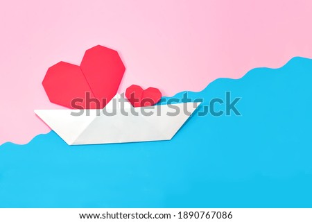 Origami paper heart in a paper boat on an abstract pink and blue background. The ship floats on the waves.