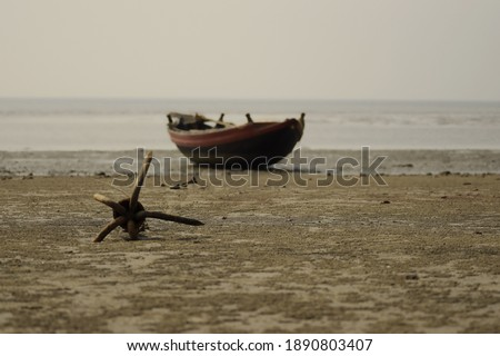 anchor hooked on the foreground at the sea beach with the local fishing boat at the background  towards the sea while picture focused on the anchor flukes at kargil beach, frezarganj, west bengal