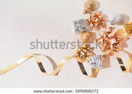 Decorative present boxes, balls, golden streamer and decorative bows on white glittering background. Party and festive concept. Top view. Flat lay.