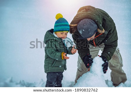 Cute Little Baby Boy with Father Having Fun Outdoors in Winter Time. With Pleasure Build Snowman. Enjoying Winter Holidays Together. Royalty-Free Stock Photo #1890832762