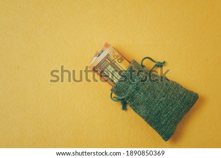 gray canvas bag with rolled up banknotes on a yellow background #1890850369