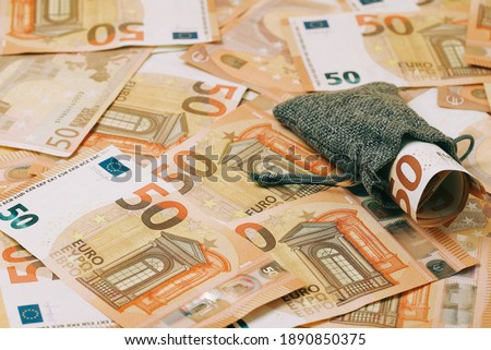 bag with rolled up money on the bottom of 50 euro banknotes #1890850375