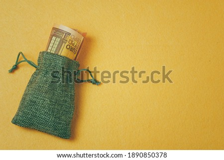 gray canvas bag with rolled up banknotes on a yellow background #1890850378