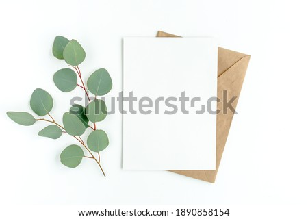 Mockup invitation, blank greeting card and green leaves eucalyptus. Flat lay, top view. Royalty-Free Stock Photo #1890858154