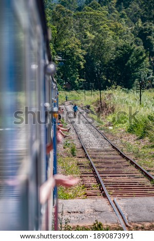 Typical train ride in Sri Lanka with people hanging out of the cabins. This picture was taken on a really hot summer day.