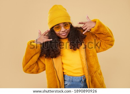 Stylish hipster black curly haired girl in trendy glasses and bright colorful warm clothes and hat doing rock gesture while standing against beige background