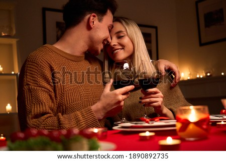Happy young couple in love hugging holding glasses, drinking wine, celebrating Valentines day dining at home together, having romantic dinner date with candles sitting at table, embracing and bonding. Royalty-Free Stock Photo #1890892735