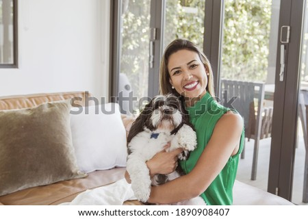 Portrait of beautiful Brazilian woman and her pet shih tzu dog at home, best friend, family love, women's day concept Royalty-Free Stock Photo #1890908407