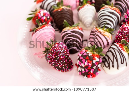 Variety of chocolate dipped strawberries on a pink cake stand. Royalty-Free Stock Photo #1890971587