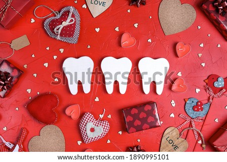 White teeth surrounded by gifts and hearts on red background. Dental Valentine card. Valentine's day concept.