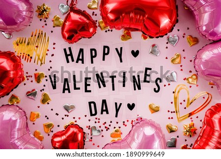 Stylish text frame with the inscription happy valentines day. Pink, red and gold hearts all around. Foil balloons top view of Valentine's Day. Copyspace. Royalty-Free Stock Photo #1890999649