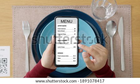 Hand's customer scan QR code for online menu service at table in restaurant during pandemic coronavirus. New normal contactless technology lifestyle protection coronavirus pandemic in restaurant Royalty-Free Stock Photo #1891078417