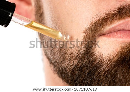 Closeup of male face and pipette with a oil for a beard growth Royalty-Free Stock Photo #1891107619