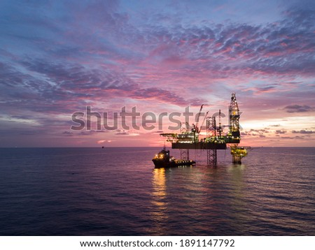 Aerial view offshore drilling rig (jack up rig) at the offshore location during sunset Royalty-Free Stock Photo #1891147792