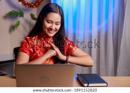 Young beauty happy Asian woman wearing Chinese tradition dress making video conference greeting and celebrating Chinese new year at home. Royalty-Free Stock Photo #1891152820