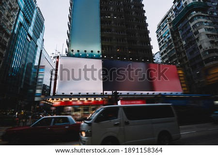 Contemporary automobiles with headlights turned on driving along asphalt road near modern buildings in downtown of city of Hong Kong #1891158364