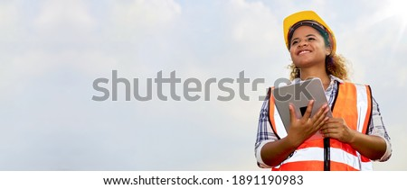 African American black female engineer or architect stands outdoors with tablet. Royalty-Free Stock Photo #1891190983