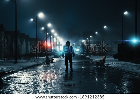 Man silhouette in misty alley at night city park, mystery and horror foggy cityscape atmosphere, alone stalker or crime person Royalty-Free Stock Photo #1891212385