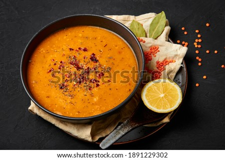 Ezogelin Soup in black bowl on dark slate table top. Turkish cuisine traditional dish with red lentils, bulgur and rice Royalty-Free Stock Photo #1891229302