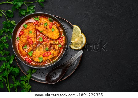 Macher Jhol in black bowl on dark slate table top. Indian cuisine Bengali Fish Curry. Asian food and meal. Top view. Copy space Royalty-Free Stock Photo #1891229335