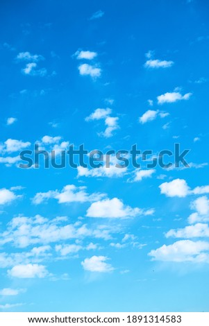 Blue sky with multitude of white clouds - vertical background Royalty-Free Stock Photo #1891314583