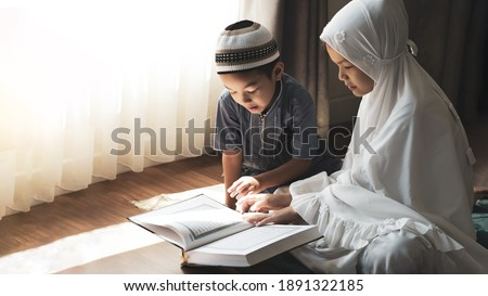 Religious Asian Muslim kids learn  the Quran and study Islam after pray to God at home .Sunset light shining through the window.Peaceful and Marvelous warm climate.  Royalty-Free Stock Photo #1891322185