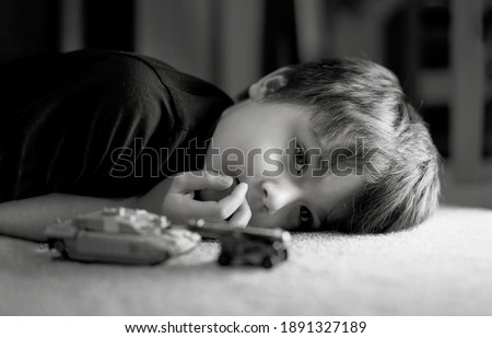 Black and white photo of lonely boy laying down on floor looking out deep in thought, Sad kid laying on carpet with tank toys.Child with bored face,Upset boy with unhappy face,Spoiled children