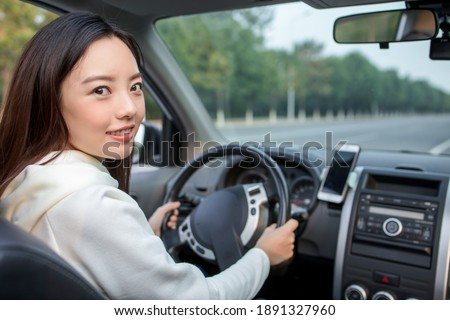 Young female driver using touch screen smartphone and gps navigation in a car. Royalty-Free Stock Photo #1891327960