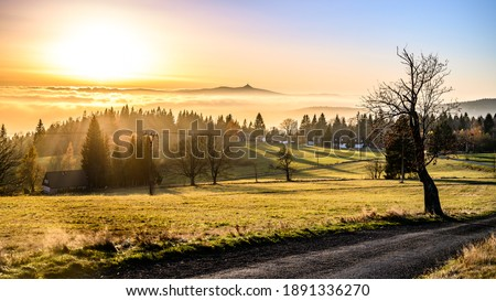 Panorama of Jested mountain ridge with silhouette of unique mountain hotel and TV transmitter. Evening weather inversion. Liberec, Czech Republic Royalty-Free Stock Photo #1891336270