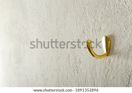 Golden little hanger on the white wall.Empty space