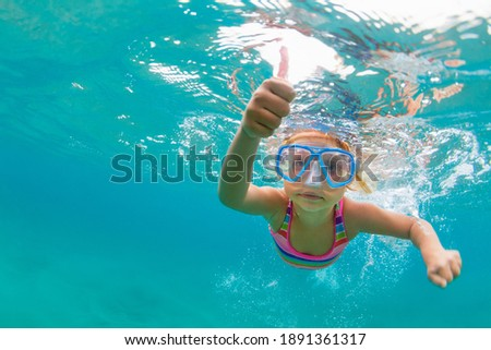 Photo of happy baby girl jump, dive underwater with fun in tropical lagoon pool. Travel lifestyle, water sport, snorkeling adventure. Family swimming lessons on summer sea beach vacation with kids