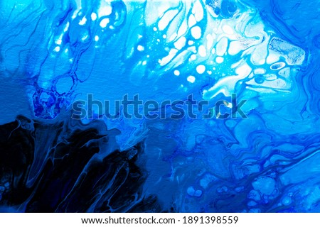 Drop of acrylic ink dissolved into water, close up view. Abstract background. Blue paint in liquid. Acrylic clouds swirling in water. Blue ink waves in liquid, abstract pattern. Blurred background